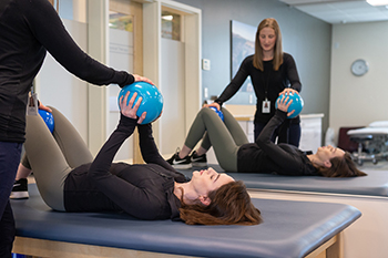 Physical therapist working with patient and medicine ball