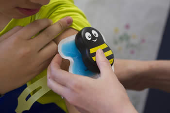 nurse puts bumble bee patch on child's arm